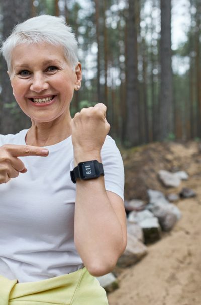 Happy fit retired female in activewear smiling broadly pointing at display of wrist smart watch, proud of calories burnt after physical activity. Mature woman using fitness tracker during morning run